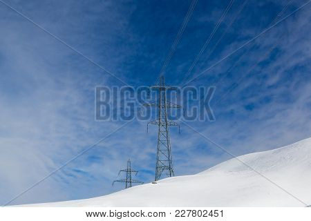 Two Electricity Pylons In Winter, White Snow, Sunny Blue Sky, Clouds