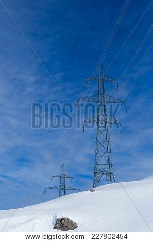 Two Tall Electricity Pylons In Winter, Snow, Sunny Blue Cloudy Sky