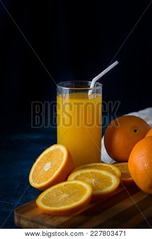 A Glass Of Fresh Orange Juice With A Tube, Orange Slices, Oranges, White Cloth On A Dark Blue Backgr