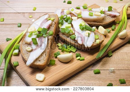 Sandwich With Bacon On Slices Of Rye Bread And Green Onions With Garlic On A Wooden Cutting Board On
