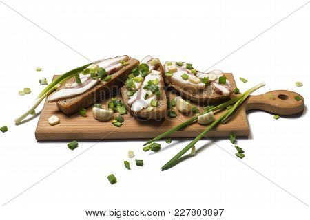 Salo On Slices Of Rye Bread And Green Onion With Garlic On A Wooden Cutting Board Isolated On White
