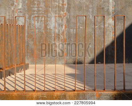 Retro Rusted Yellow Metal Fence In A Public Place