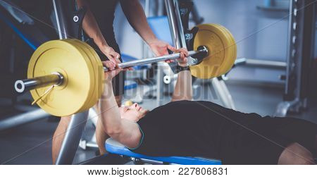 Young Man Lifting The Barbell In The Gym With Instructor .