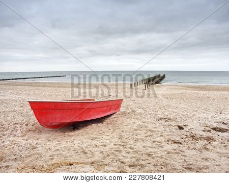 Abandoned Red Paddle Boat On Sandy Beach Of Sea.  Smooth Water Level Within Morning Windless. Dramat