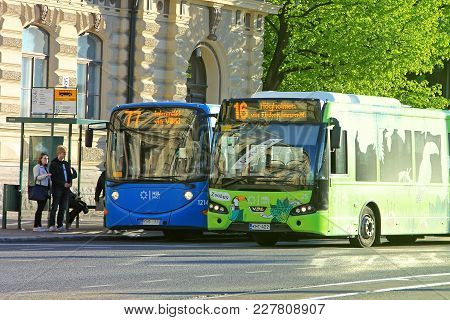 Helsinki, Finland - June 6, 2017: Two City Buses With Passengers Getting On At A Bus Stop In Central