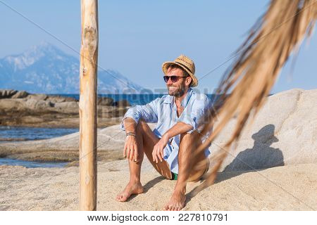 Young man relaxing on the beach, sunbathing on a rock near the sea