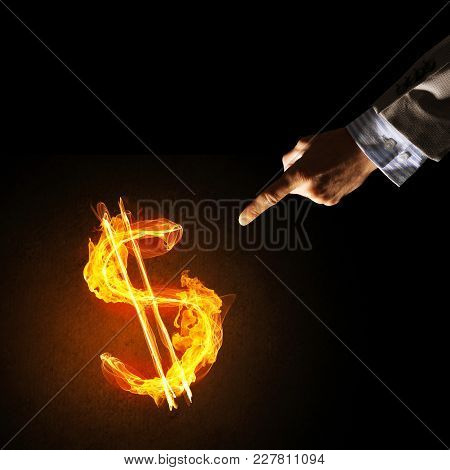 Close Of Businessman Hands Pointing At Fire Glowing Dollar Sign
