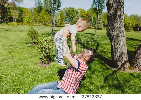 Joyful Man Walk On Green Park, Rest, Have Fun, Play, High Toss Up Little Cute Child Baby Boy Sit On
