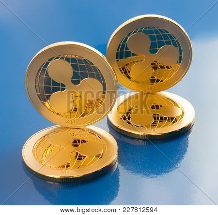 On The  Blue Background Are Gold Coins Of A Digital Virtual Crypto  Currency - Ripple. In Addition T