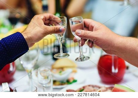 Hands With Glasses Of Vodka At A Festive Event