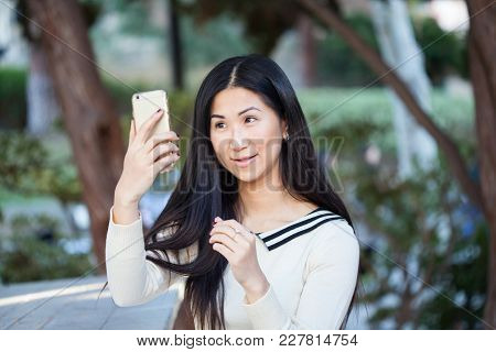A Happy Girl Gazing On Her Phone With Rapture
