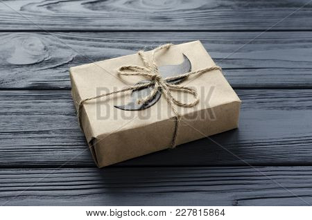 Gift Box Wrapped In Kraft Paper With Paper Mustache On Grey Wooden Background