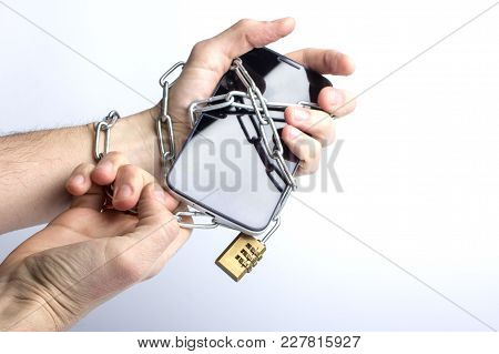 Iron Chain With Lock Ties Together Hand And Smart Phone. Mobile Phone Addiction Concept.
