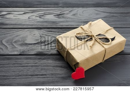 Gift Box Wrapped In Kraft Paper With Paper Mustache And Red Heart On Grey Wooden Background