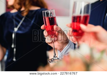 Glass Of Red Champagne In The Hand Of A Man In A Suit At The Festival Close-up. Symbolizes Success A