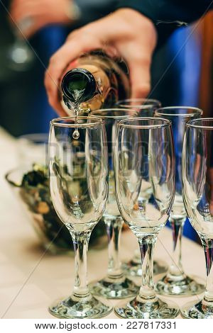 Waiter Bartender Pours Champagne From A Bottle Into Glasses At A Festive Event