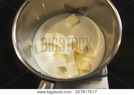 Melted Fresh Butter In A Metal Pot On Kitchen Table. Raw Materials For Baking.