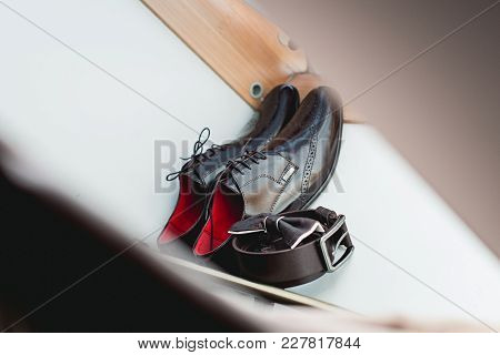 Wedding Accessories. Brown Bow Tie Lies On A Belt, Leather Shoes On Window Sill. Grooms Wedding Morn