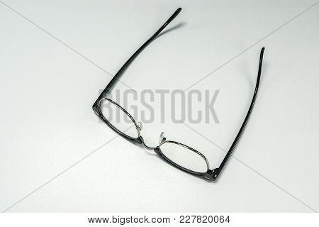 Isolated Black Modern Men Eye Glasses On Office Desk