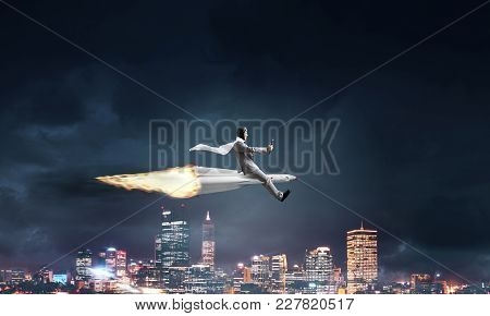Conceptual Image Of Young Businessman In Suit Flying On Rocket With Night Cityscape And Blue Sky On
