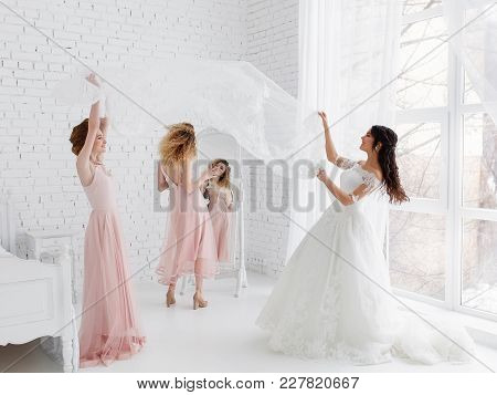 Cute Girls Celebrating A Bride's Bachelorette Party And Playing With Veil In Bedroom.