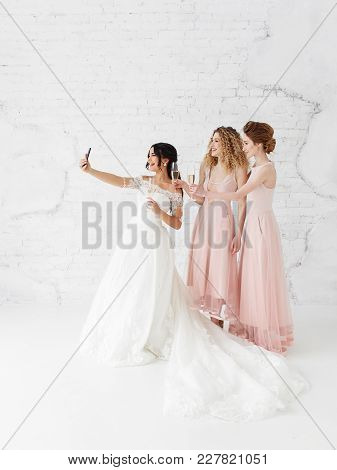 Bride And Bridesmaids Taking Selfie Together Drinking Champagne In White Studio