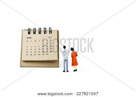 June. Two Thousand Eighteen Year Calendar And Two Miniature Plastic Figures. Man And Woman On White