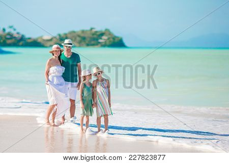 Happy Family On The Beach During Summer Vacation