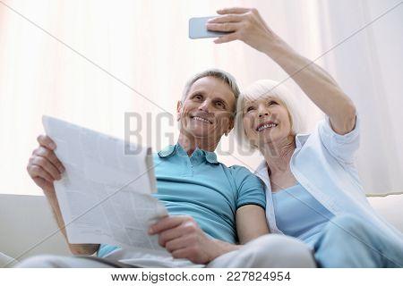 New Photo. Active Modern Pensioners Enjoying New Technologies