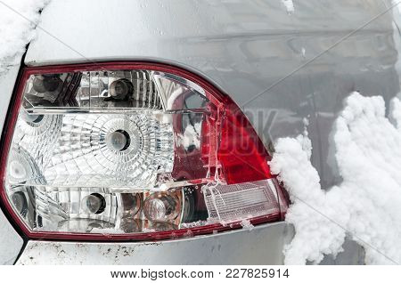 Damaged And Broken Rear Stop Or Tail Light Of The Silver Car In Crash Accident In The Winter On The