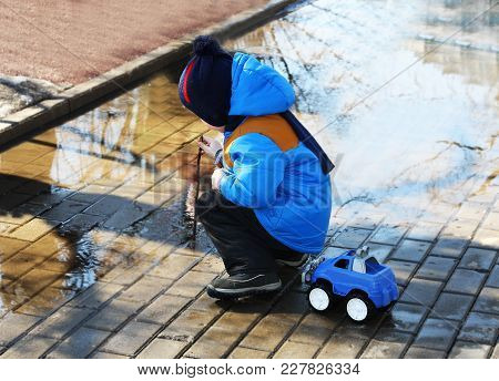 The Child Walks In The Spring On The Street.