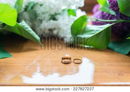 Two Wedding Golden Rings On The Wooden Background.
