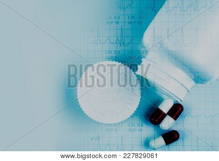 Capsule Pills And Opened Bottle And Ekg Or Ecg (electrocardiogram) Graph Report Paper. Est ( Exercis