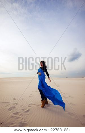 Beautiful Young Woman, Wearing In A Flying Blue Scarf, Is Walking In The Desert, Looking Into The Ca