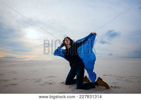 Expressive Girl, Wearing In A Flying Blue Scarf, Fights The Wind In The Desert - On The Beginning Of