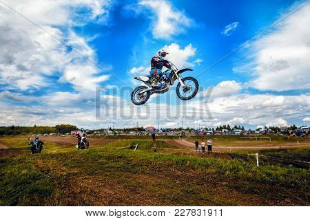 Racer On Motorcycle Dirtbike Motocross Cross-country In Flight, Jumps And Takes Off On Springboard A