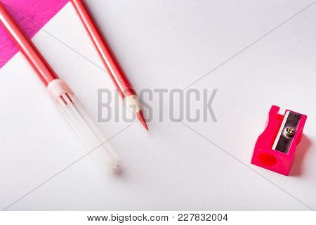 Red Pencil With Pencil Sharpener And Red Felt Pen On White Paper Sheet. Stationery. Office Tool.