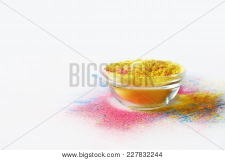 Indian Holi Festival Yellow Colour In Bowl On White Background. With Text Space