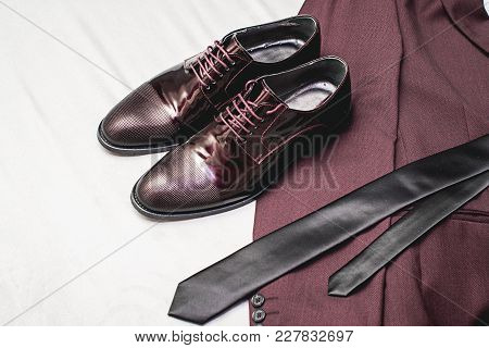 Suit, Necktie, Leather Shoes On A White Textile. Grooms Wedding Morning. Close Up Of Modern Man Acce