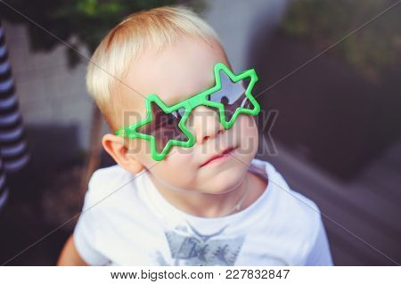 Happy Blond Boy With Glasses Star Looks Up Into The Camera Smiling. Soft Warm Toning