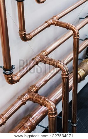 Copper Pipes And Fittings For Carrying Out Plumbing. Copper Pipe In Front Of A White Wall