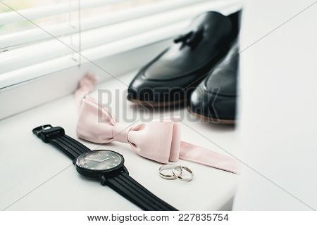 Close Up Of Modern Man Accessories. Beige Bow Tie, Black Leather Shoes, Belt And Watch. Close Up Of