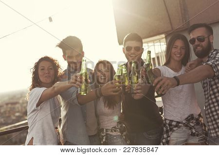 Group Of Young Friends Having Fun At Rooftop Party, Making A Toast With Beer Bottles And Enjoying Ho