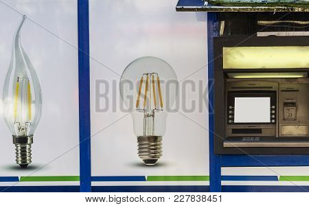 Two Bulbs And One Atm For Cash Withdrawal. Graphic Background. Energy-saving Bulbs For Home And Offi