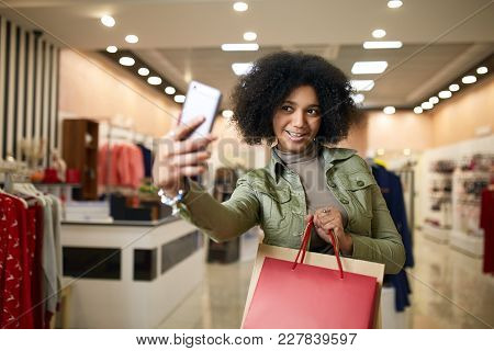 Cute African American Woman Taking Selfie With Shopping Bags And Smiling Near Clothing Store. Black
