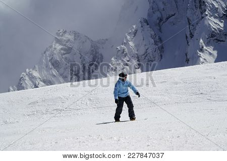 Snowboarder Downhill On Snowy Ski Slope In High Mountain At Sun Winter Day. Caucasus Mountains In Ha