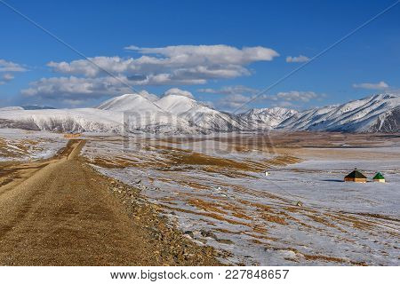 Autumn Steppe With A Gravel Winding Road, Snow-capped Mountains, River And Golden Vegetation Against