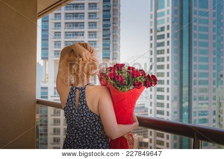 Still Life Romantic Dreams Of A Girl With A Bouquet Of Red Roses On The Balcony Of A High-rise Build