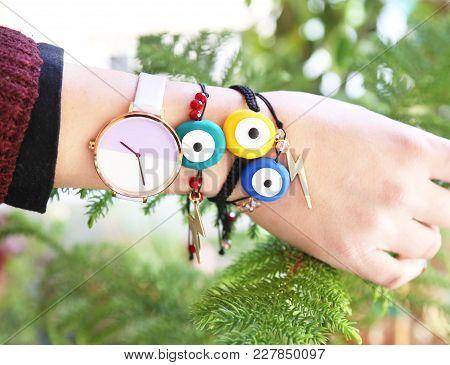 Woman Hand Wearing Stylish Evil Eye Bracelets - Greek Jewelry Advertisement