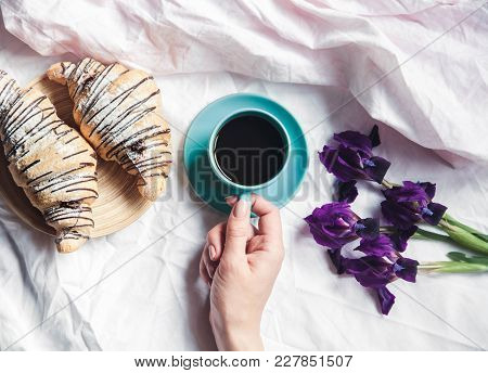 Woman Hands Holding Cup Of Coffee In Bed. Beautiful Flowers And A Watch With A Bracelet A